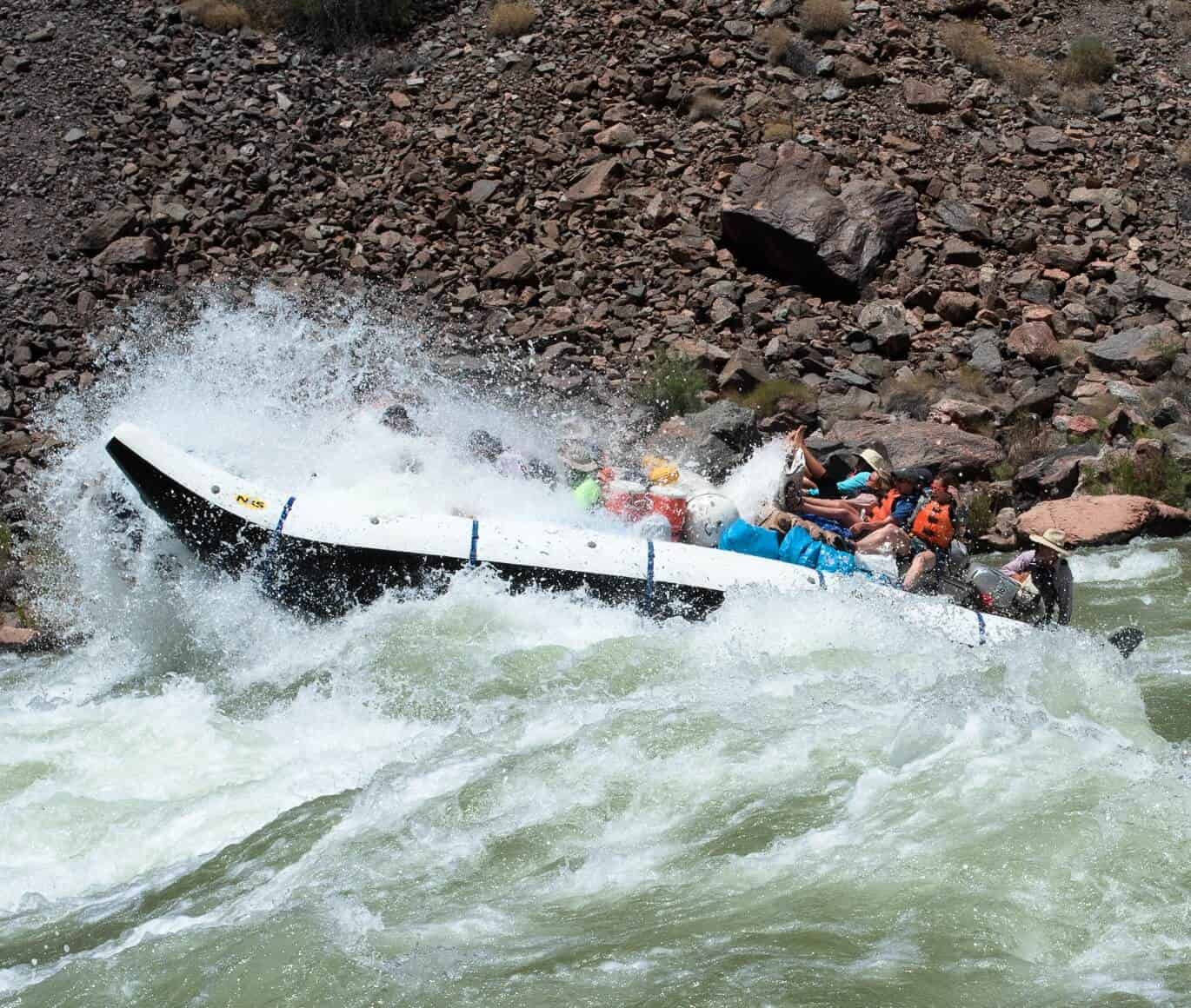 Motor raft going through a rapid while Grand Canyon Rafting